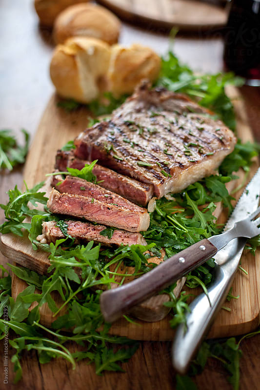 Beef steak with rocket salad by Davide Illini for Stocksy United