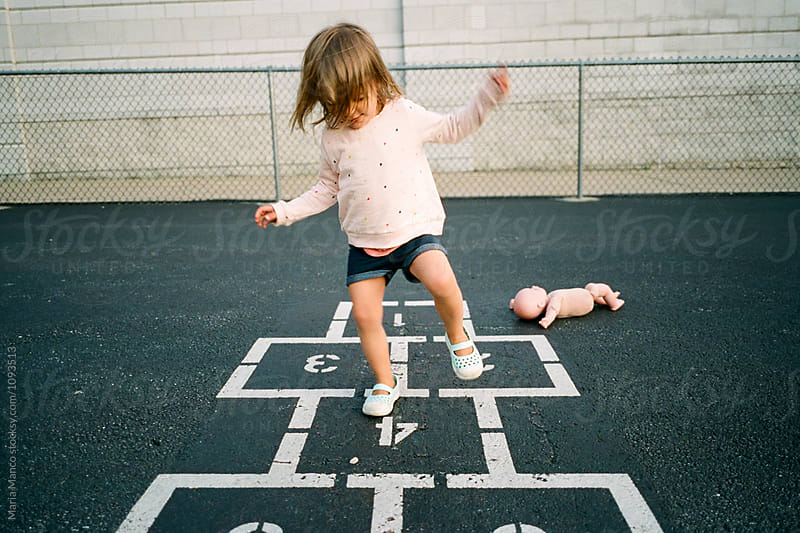 child playing hopscotch  by Maria Manco for Stocksy United