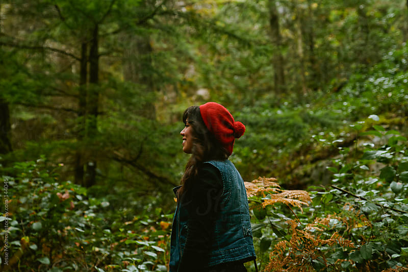 female looking into the woods by Jesse Morrow for Stocksy United
