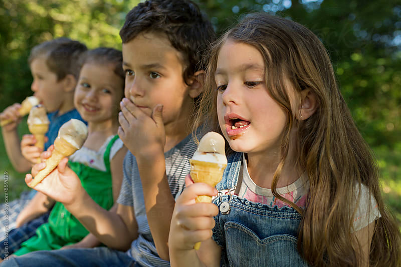 Children eating ice cream. by Dejan Ristovski for Stocksy United