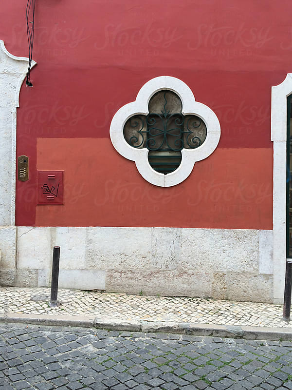 Red building facade with quatrefoil window in Lisbon, Portugal by Amanda Large for Stocksy United