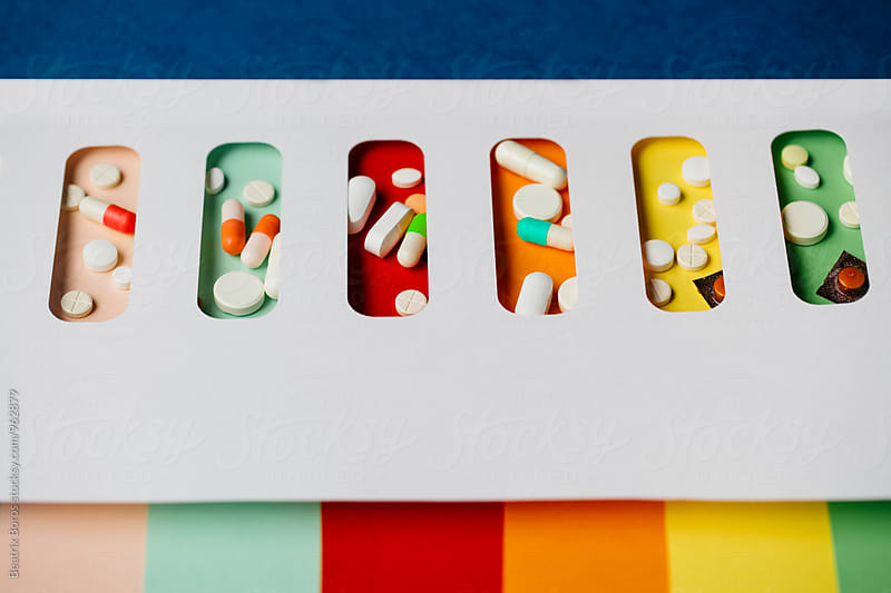 Capsules and drugs in colorul holders by Beatrix Boros for Stocksy United