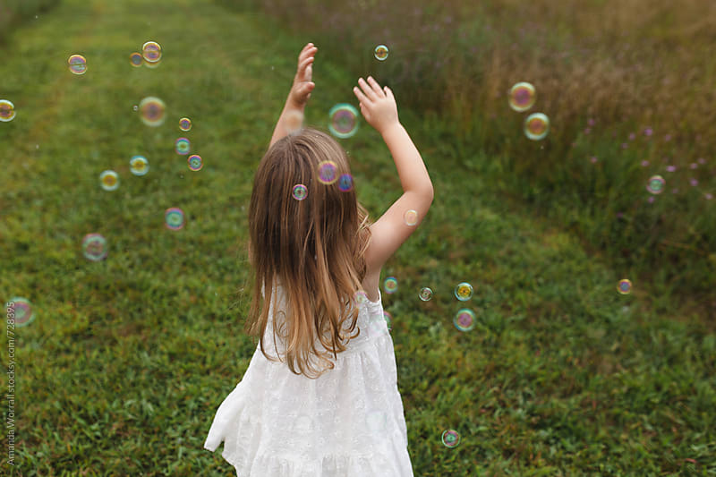Girl reaching up to pop bubbles over her head by Amanda Worrall for Stocksy United