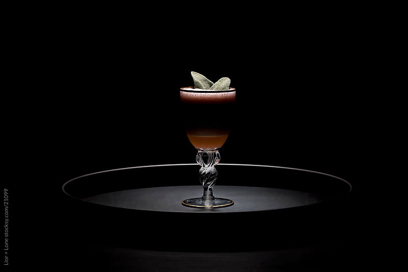 Small dark layered cocktail on tray by Lior + Lone for Stocksy United