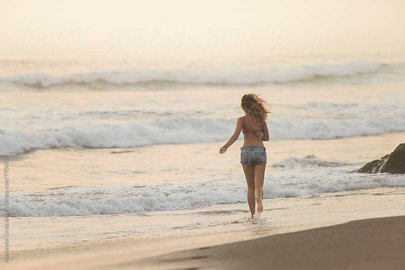 Woman Enjoying The Sunset On The Beach by Alexander Grabchilev for Stocksy United