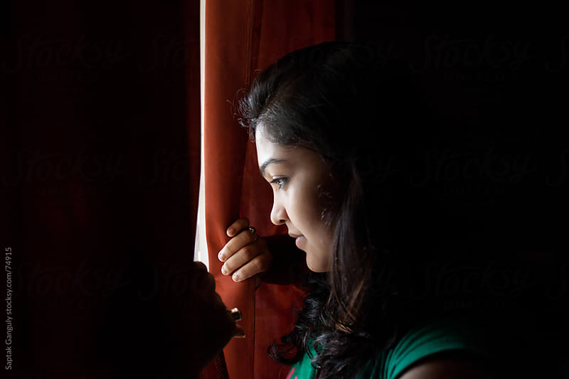 Girl looking through window by Saptak Ganguly for Stocksy United