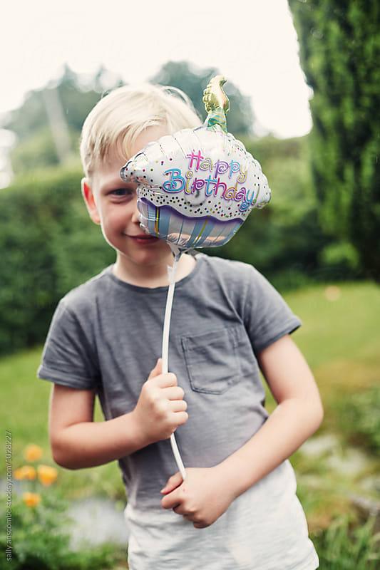 Child holding a happy birthday balloon