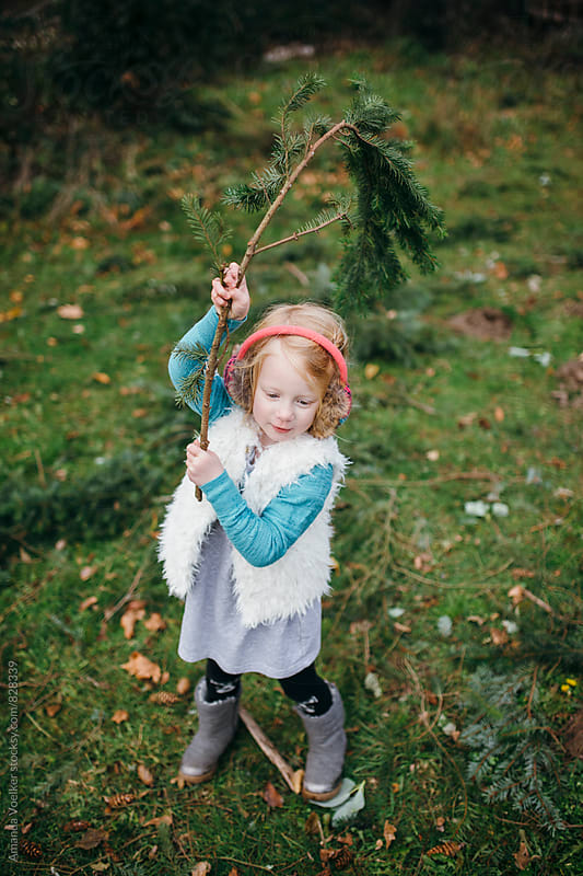Little Girl Stands with a Large Pine Branch Over her Head by Amanda Voelker for Stocksy United