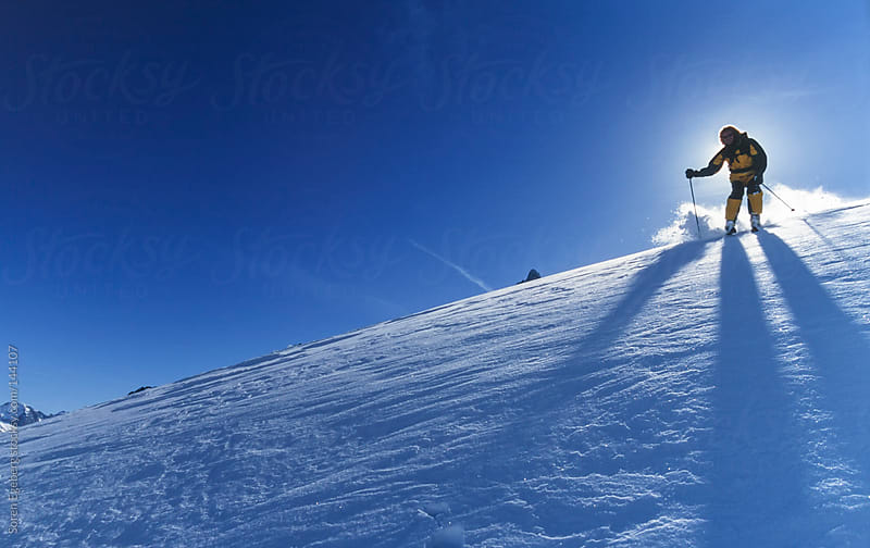 Man skiing powder snow in winter mountains backlit by sun and blue sky by Soren Egeberg for Stocksy United