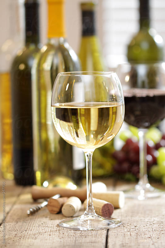 Glass of white wine with bottles in background by Sandra Cunningham for Stocksy United