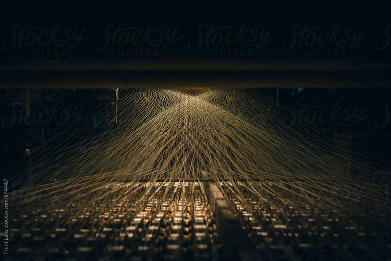 View of loom reels and illuminated threads stretching by Trent Lanz for Stocksy United