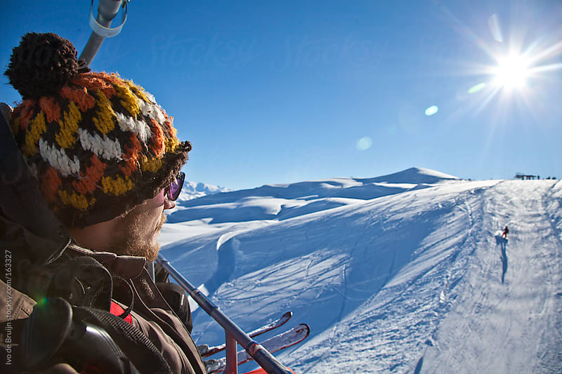 Young man looking at the slopes from a chairlift by Ivo de Bruijn for Stocksy United
