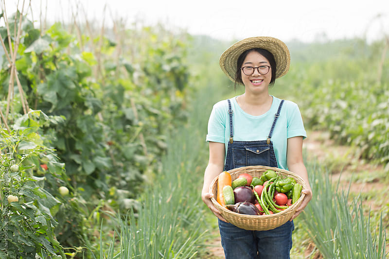 Young Chinese girl holding vegetable grown on farm by Maa Hoo for Stocksy United