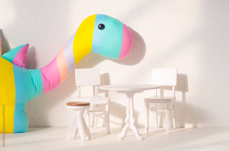 Toy dinasaur in a dollhouse by Alita Ong for Stocksy United