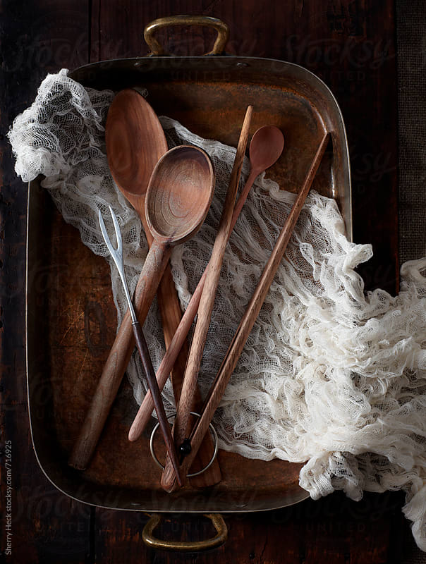Long wooden spoons nestled in cheesecloth and copper roasting pan by Sherry Heck for Stocksy United