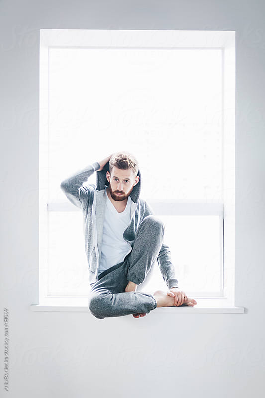Man in a grey hoodie and sweat pants sits at a window by Ania Boniecka for Stocksy United