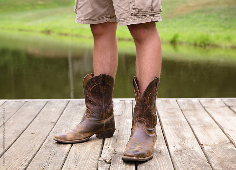 Teenage boy standing on a dock in cargo shorts and cowboy boots by Carolyn Lagattuta for Stocksy United