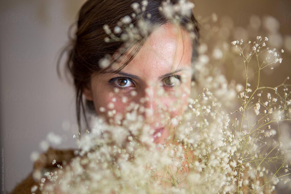Hide And Seek Woman Hiding Behind Small White Flowers Stocksy United