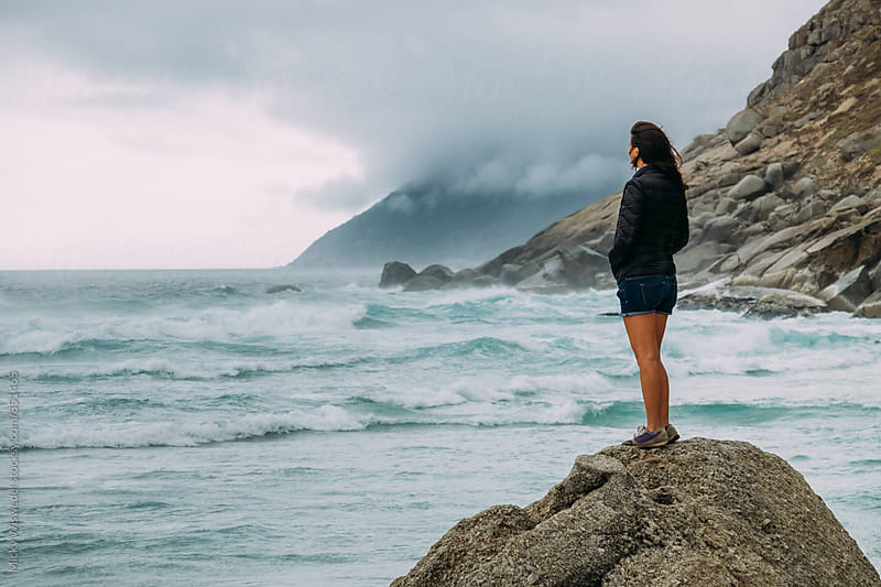 Woman standing on a rock looking out to sea on a stormy day by Micky Wiswedel for Stocksy United