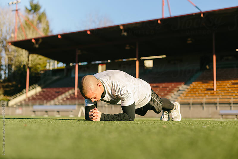 Athletic Man In Plank Position On Turf Field During Workout Routine by Luke Mattson for Stocksy United