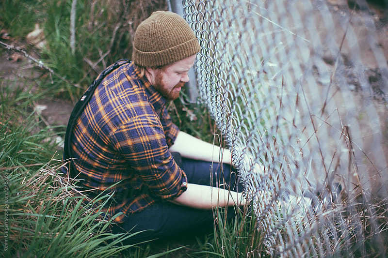 Man Climbing Under a Fence by Kevin Gilgan for Stocksy United