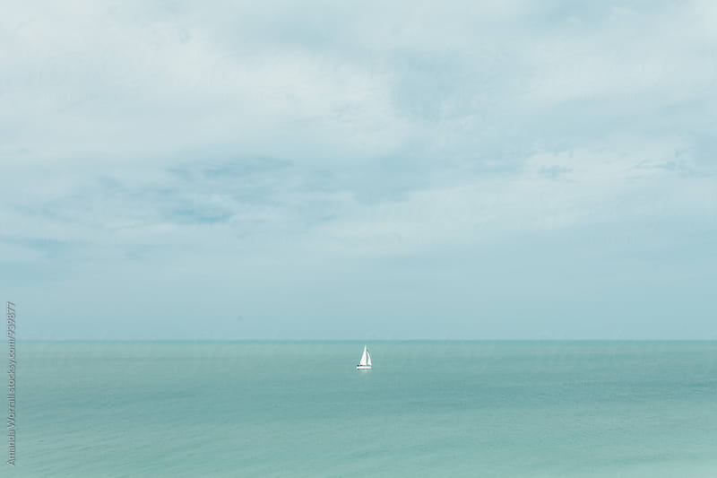 Horizontal scene of a white sailboat centered in calm waters by Amanda Worrall for Stocksy United