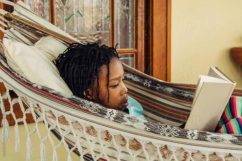 Black girl reading a book in a hammock by Gabriel (Gabi) Bucataru for Stocksy United