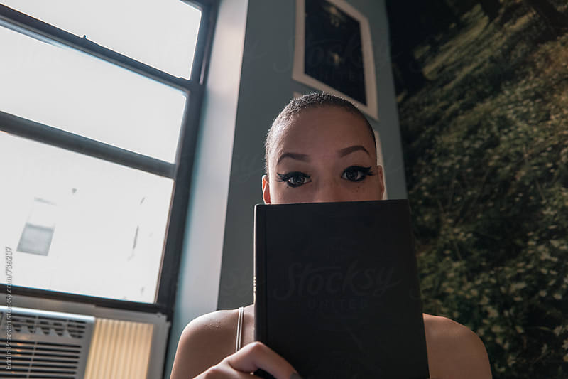Beautiful young woman holding a book up to her face by Eddie Pearson for Stocksy United