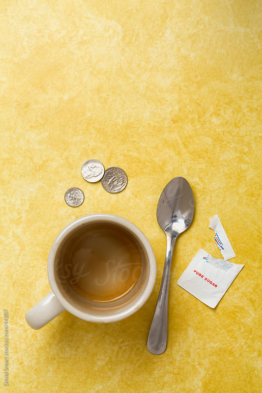 Empty retro coffee mug, spoon, sugar packet and tip on diner counter by David Smart for Stocksy United