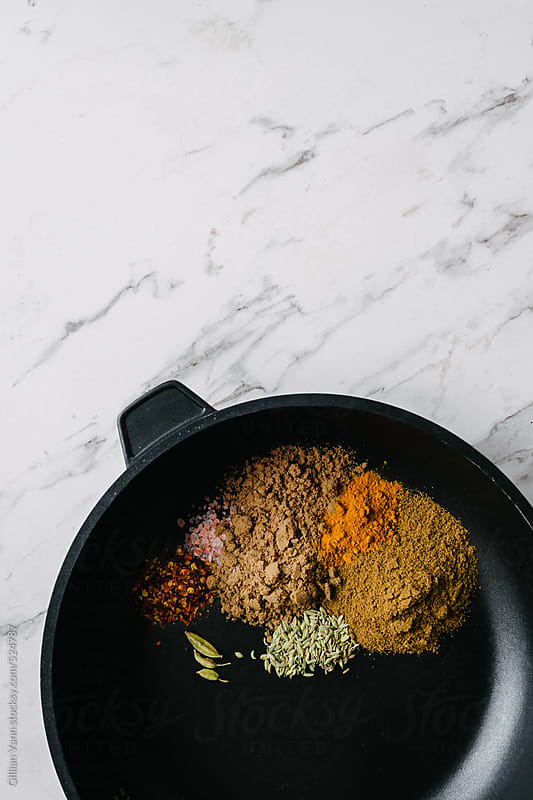 ground spices in a frypan on a marble background by Gillian Vann for Stocksy United
