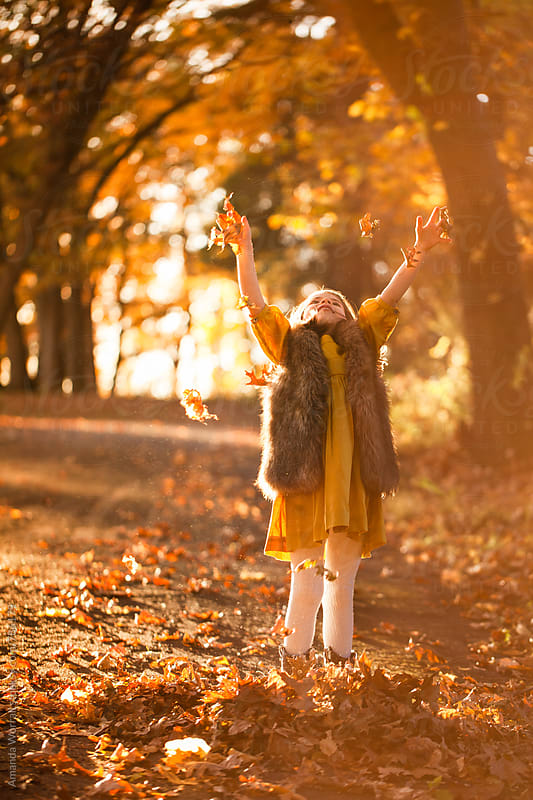 A happy young girl throwing leaves in the air during autumn by Amanda Worrall for Stocksy United