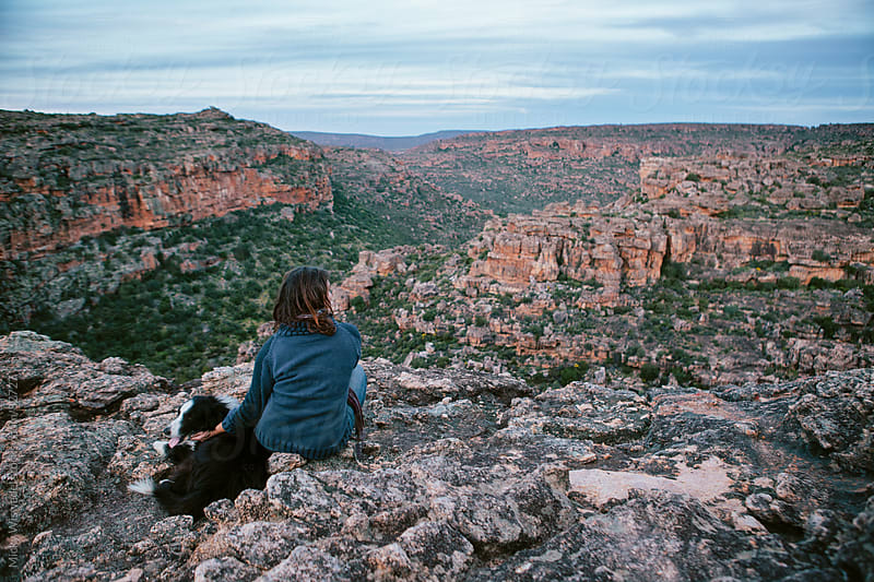 Woman enjoying a peaceful scenic view with her dog by Micky Wiswedel for Stocksy United
