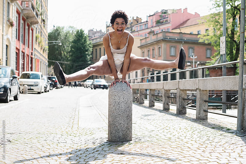 Happy young woman having fun in the city by Simone Becchetti for Stocksy United