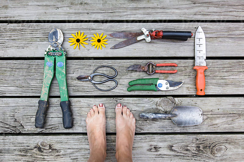 A women's feet surrounded by garden tools on a wooden deck. by Holly Clark for Stocksy United