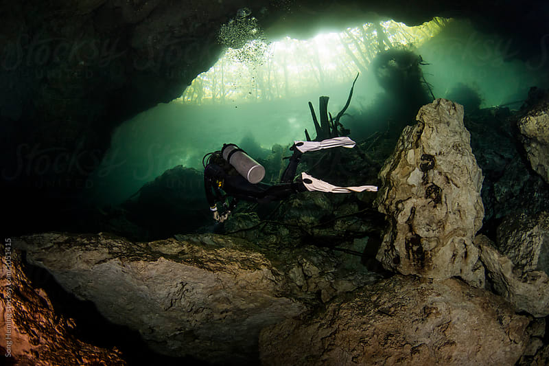A scuba diver swimming in Mexico's  Cenote Chac-Mool by Song Heming for Stocksy United