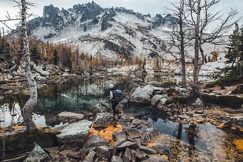 Backpacker treks in rugged landscape by Tari Gunstone for Stocksy United