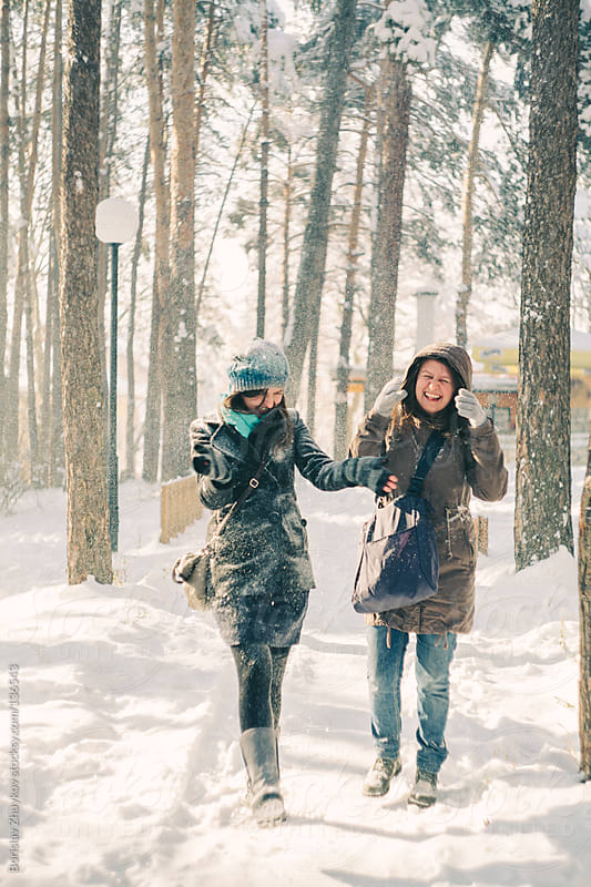 Two joyful and energetic girlfriends having fun in the snow during a cold winter day by Borislav Zhuykov for Stocksy United
