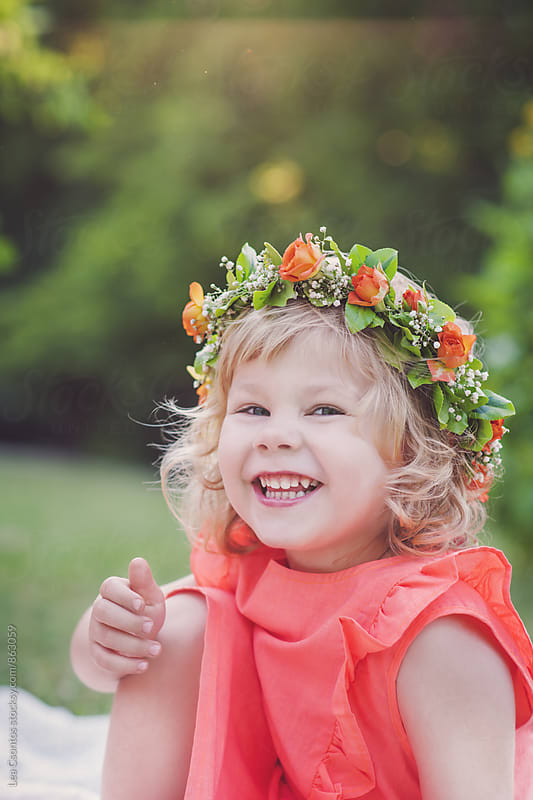 Beautiful laughing little girl sitting on a field wearing a flower crown by Lea Csontos for Stocksy United
