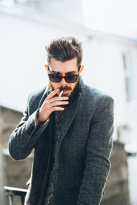 Handsome Bearded Man Smoking Outdoors by Nemanja Glumac for Stocksy United
