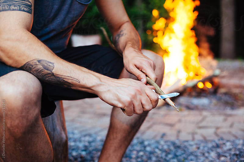 A caucasian man whittling a stick outdoors for roasting s'mores.  by J Danielle Wehunt for Stocksy United