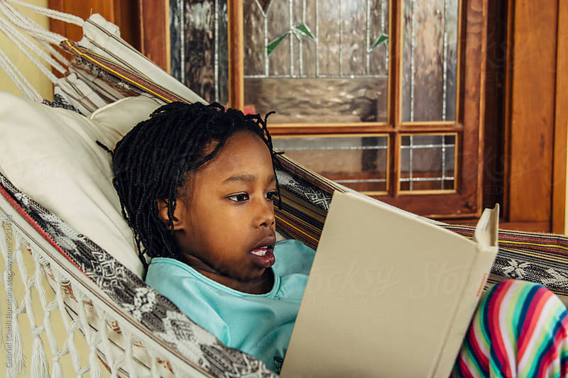 Young black girl reading a book by Gabriel (Gabi) Bucataru for Stocksy United