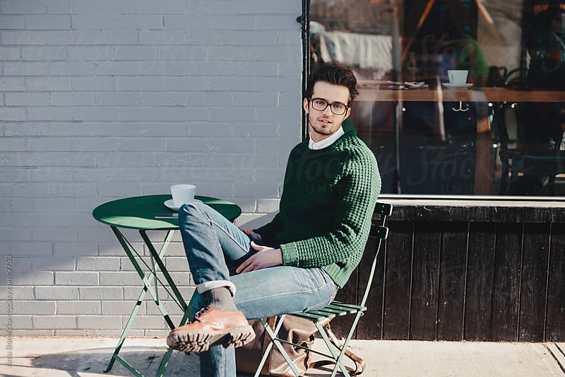 Man sitting on a patio looking at camera by Ania Boniecka for Stocksy United