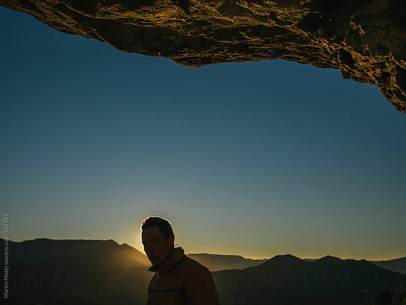 Man hiking by the sunset under cliff by Martin Matej for Stocksy United