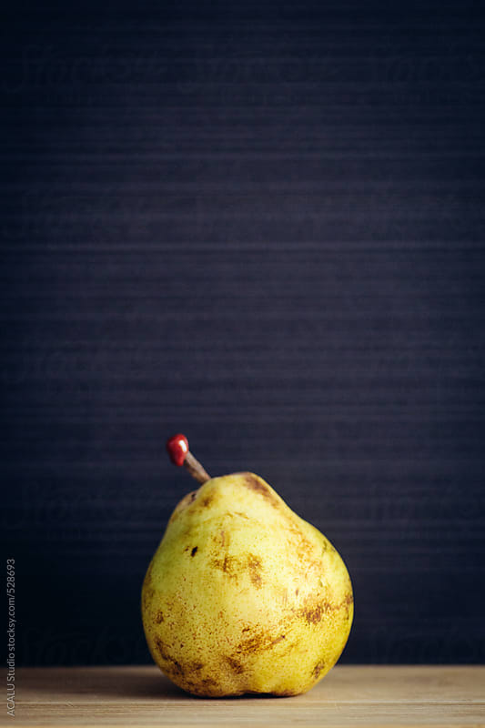 Yellow pear with red seal on black background by ACALU Studio for Stocksy United
