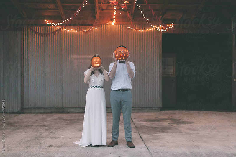 Wedding Couple with Jack-O-Lantern Decorations over their Faces by Briana Morrison for Stocksy United