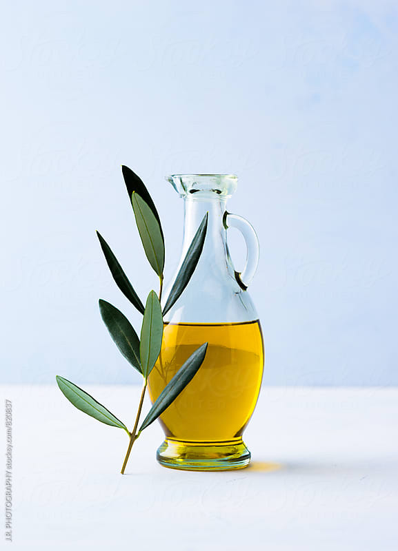 Jug of olive oil and twig of olive tree by J.R. PHOTOGRAPHY for Stocksy United