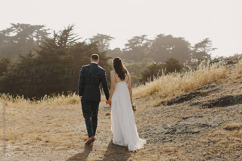 Bride and Groom Walking Away in Field by Sidney Morgan for Stocksy United