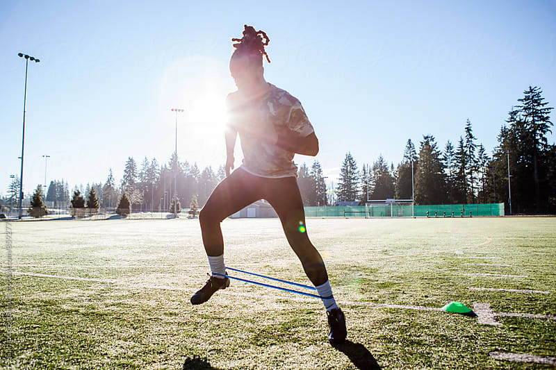 African American athlete  training on a football field by Suprijono Suharjoto for Stocksy United
