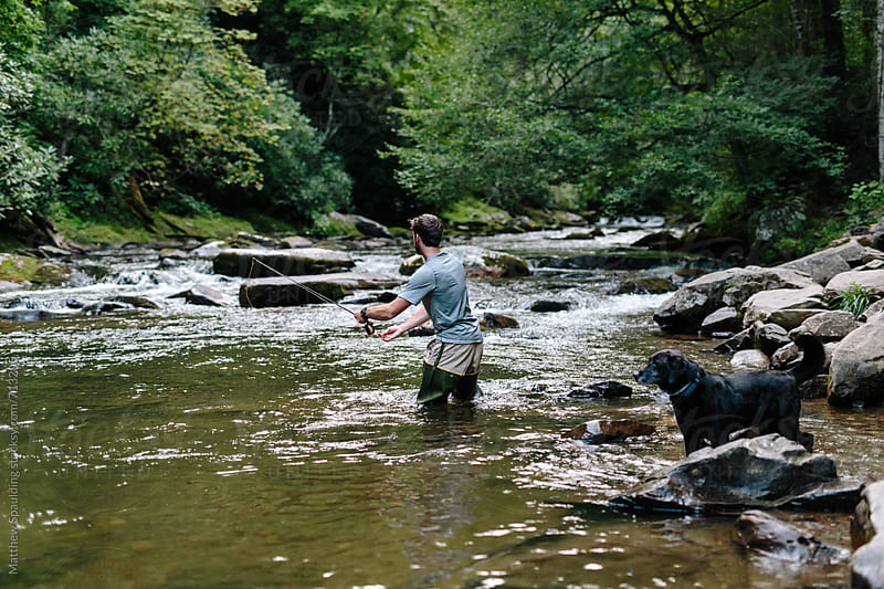 Man fly-fishing in clear river trying to catch fish by Matthew Spaulding for Stocksy United