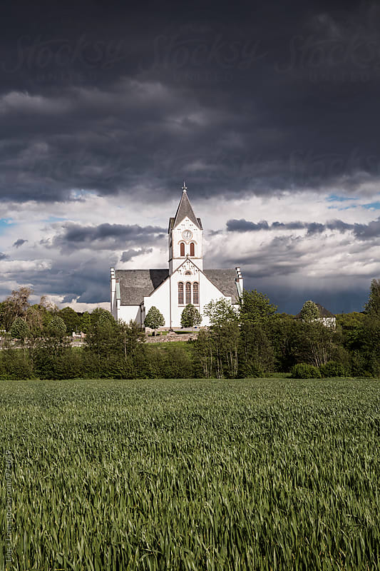 Scandinavian church in Denmark under a dramatic stormy sky by Lior + Lone for Stocksy United